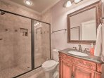 The downstairs bathroom features a lavish walk-in shower and single vanity.