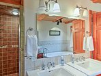 Wash up in the second bathroom, equipped with 2 single vanities, a walk-in shower, and a lavish tub.