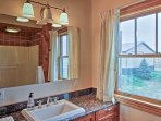The first bathroom features a his-and-hers vanity and shower/tub combo.