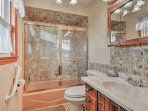 You'll feel as though you're at a resort in this private stone bathroom.