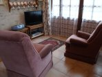 Sitting area with TV (UK and French) comfortable chairs and french window too the patio