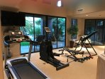 Private gym with sliding walls of glass looks over the Oasis courtyard.