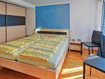 The bedroom has a double bed with two single matrasses.
