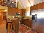 The kitchen features stainless steel appliances and a bar counter