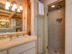 The stand-alone shower features a waterfall shower head and beautifully accented tilework.
