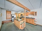 The kitchen is fully equipped with stainless steel appliances, cookware, and dishware.