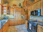 Cook with ease in this beautiful kitchen which features rustic pine cabinetry and dark granite countertops.