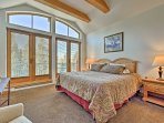 The master is complete with high ceilings, wood beams, views, and a king bed.