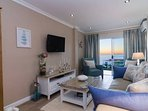 Stylish lounge leading to a private balcony with stunning sunset ocean views
