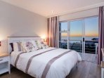 Ensuite master bedroom with a queen sized bed and stunning ocean views