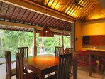 Annex living/dining area overlooking the pool and rain-forest background.