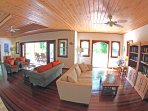 Wide angle shot showing the spacious living room with doors opening onto the patio and garden.