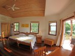 Wide angle photo of the spacious bedroom #2 overlooking the garden and pool area.