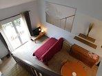 Séjour et escalier d'accès à la chambre. Porte fenêtre donnant sur terrasse privative