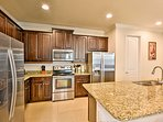 The fully equipped kitchen features stainless steel appliances and granite countertops.