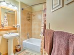 The second bathroom is equipped with a single vanity and shower/tub combo.