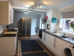 Kitchen (fully kitted) leading  to rear garden and hot tub.  Washing machine/Dryer and dishwasher