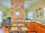Around the corner from the original decorative brick fireplace is the fully equipped kitchen.