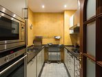 Modern, fully-equipped kitchen with oven, washing machine and dishwasher.
