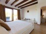 Master bedroom with private balcony overlooking garden & pool