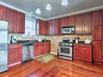 Utilize the stainless steel appliances and granite countertops, all highlighted by surrounding red wood elements.