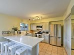 The fully equipped kitchen features stainless steel appliances and an expansive counter.