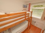 The small bedroom in Chalet 184 has pine bunk beds