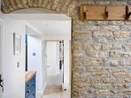 The entrance hall showcases an original Cotswold stone wall