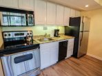 The kitchen features granite countertops, a dishwasher, electric oven & stove, microwave, refrigerator and coffee maker.