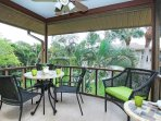 Second story secure lanai with palm frond privacy screening overlooking tropical landscape.