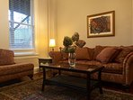The cozy living room has a brass chandelier and the sofa is large enough to sleep on.
