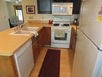 Kitchen:  Another view that highlights the stovetop, oven, microwave, dishwasher, and dual sinks.