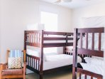 The fourth bedroom with two bunk beds, flat screen TV, game system, and board games.