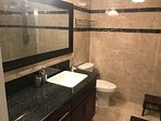 All marble bathroom with large walk in shower stall