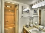 The modern, clean bathroom features a shower-tub combination.