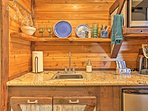 Beautiful granite countertops, a re-purposed cedar backsplash and custom cabinets create a unique touch in the...