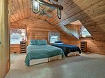 This bedroom offers a queen bed and twin bed.