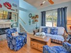 The open and airy living space boasts comfy sofas and nautical decor.