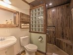 The bathroom features stained concrete flooring, a walk-in tile shower with rain head, glass block shower wall, dual...