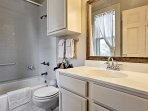Wash up in the first bathroom, equipped with a single vanity & shower/tub combo.
