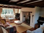 Triple aspect sitting room with wood burner, TV, stereo and piano.