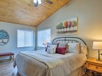 The master bedroom features beautiful vaulted ceilings and a king-sized bed.