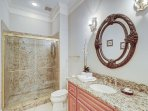 The 4th bathroom features a granite vanity and glass-door shower.