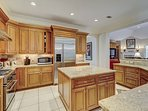 Chef's kitchen with center island, granite countertops, and stainless steel appliances.