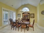 Light-filled dining area for 8 with vaulted ceilings and elegant chandelier.