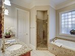 En-suite master bath with jetted tub, shower, dual granite vanities, and two walk-in closets.