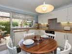 This kitchen is modern and bright and has a door out to the sunny courtyard
