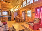 Rustic wood paneling, vaulted ceilings, and large windows embellish the open living space.