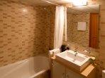 Tres baños. Uno con bañera, aseo, bidé y mueble con lavamanos