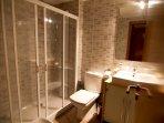 El segundo baño con ducha grande, aseo, bidé y meuble con lavamanos. También con secadora de pelo